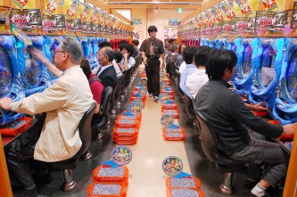 Customers try their luck at a Pachinko parlour in Tokyo on Saturday, June 9, 2007. While there is no direct monetary return in the game, pachinko pinball parlours at least give Japanese gamers the feeling of gambing. Photographer:Robert Gilhooly/Bloomberg News